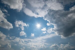 Blue sky with fluffy clouds and sun